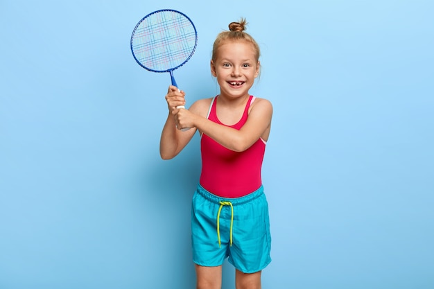 Cute small female child plays badminton with friends