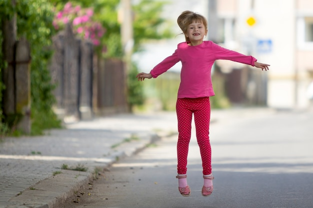 Cute small funny smiling toothless girl in pink casual clothing with long blond pony tail jumping