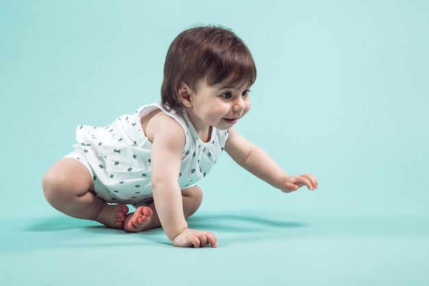 Cute small girl crawling sitting in studio on blue background