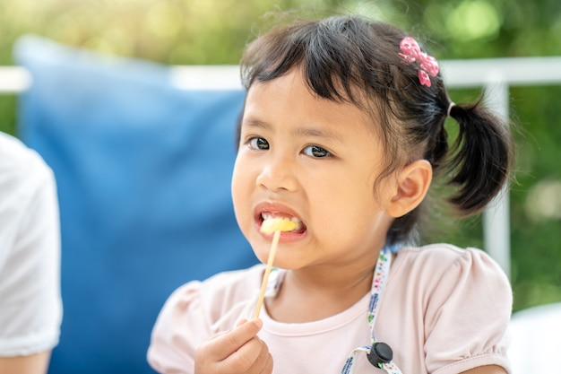 かわいい小さな女の子は、屋外でランチにフライドポテトを食べることをお楽しみください