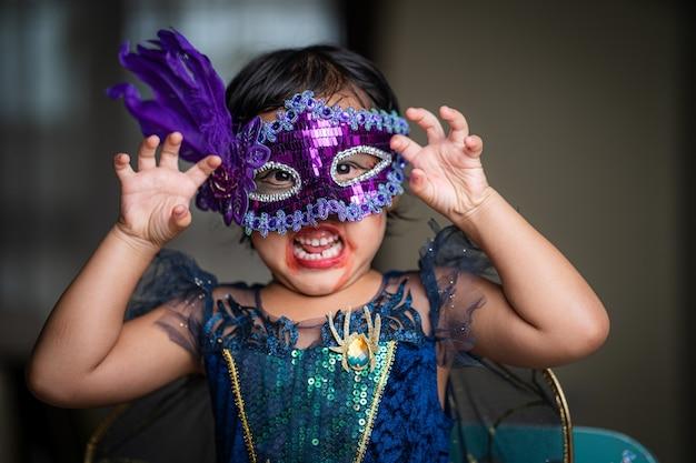 실내에 앉아 보라색 마스크를 쓰고 할로윈 의상을 입은 귀여운 작은 소녀