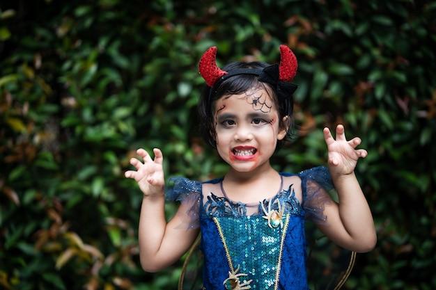 야외에 서 있는 얼굴 표정으로 할로윈 의상을 입은 귀여운 작은 소녀