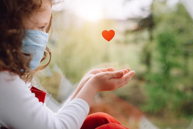 귀여운 작은 소녀는 코로나 바이러스 covid-19 전염병 동안 병원에서 일하는 의사와 의료진에게 감사를 표시하는 방법으로 작은 심장 근처의 문턱에 앉아 얼굴 파란색 마스크를 착용