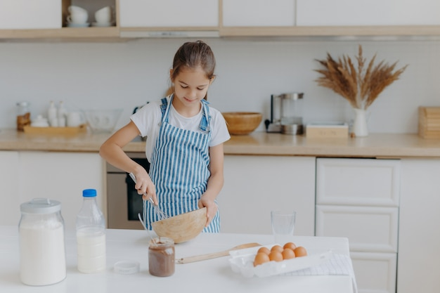 Cute small girl wears striped apron, whisks ingredients in bowl, prepares dough, teaches to cook