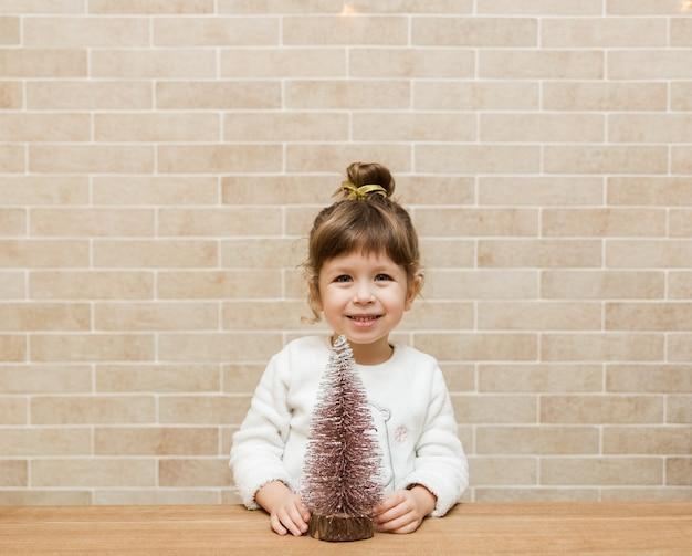 크리스마스 tree.brick 벽과 귀여운 작은 소녀. 미니멀리스트 스타일
