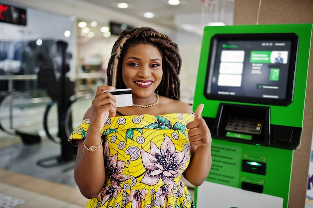 Cute small height african american girl with dreadlocks, wear at coloured yellow dress, against atm with credit card at hand.