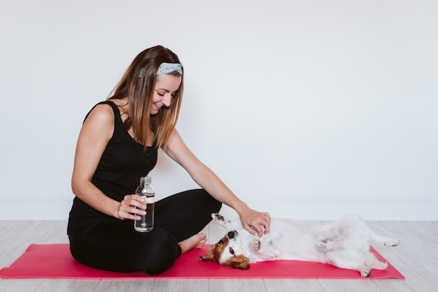 Cute small jack russell dog sitting on a yoga mat at home with her owner drinking water.