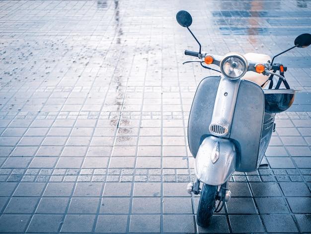 雨の日の敷石駐車場でかわいい小さなバイクスクーター