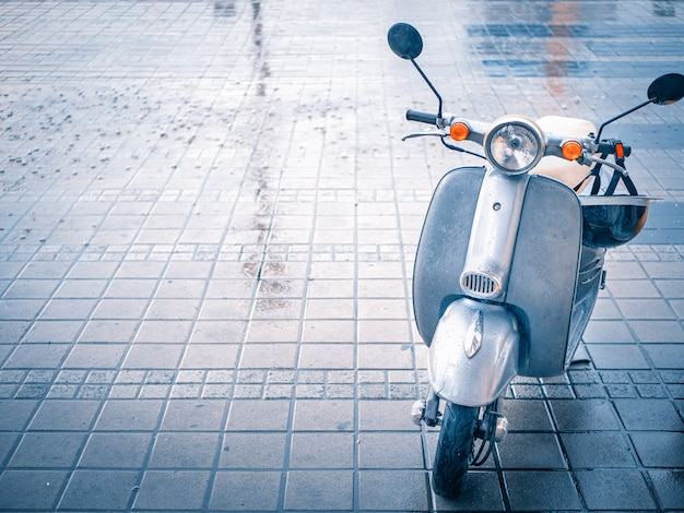 Cute small motobike scooter at paving stone parking at rainy day