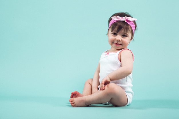 Cute small smiling girl with pink bow in hair sitting in studio posing on blue background
