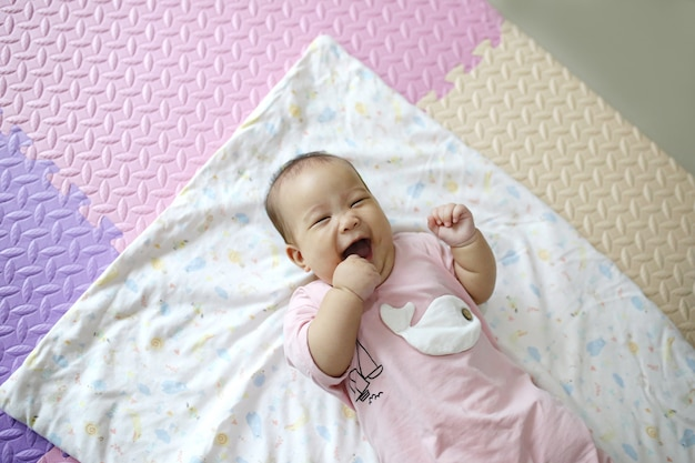 Cute smart asian newborn baby sleeping with teddy rabbit toy on pink soft bed at home.
