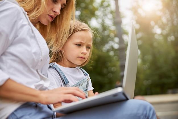 그녀의 엄마가 뭔가 세부 사항을 말하는 동안 귀여운 스마트 어린 소녀 듣고 노트북에서 수업을 학습