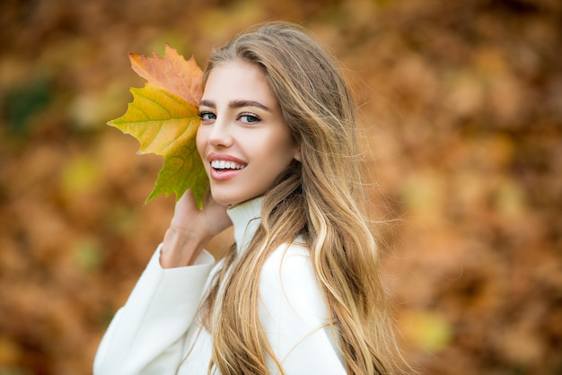 Cute smile woman holding autumn leafs in the nature outdoor. happiness carefree.