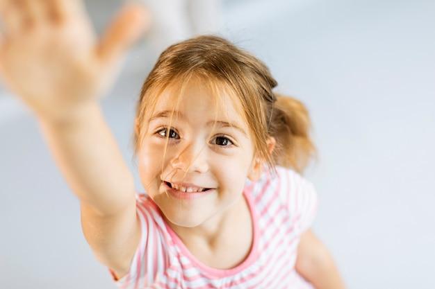귀여운 웃는 소녀 손을 앞으로 상승