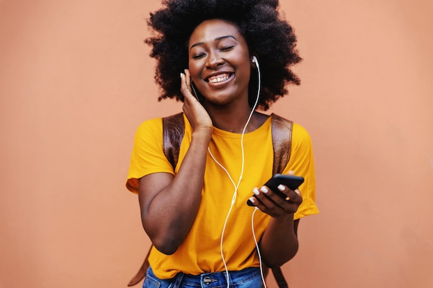 Cute smiling african girl standing outdoors and enjoying music.
