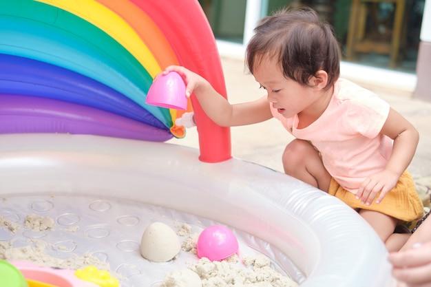 집에서 모래 상자에서 운동 모래를 가지고 노는 귀여운 웃는 아시아 2세 유아 소녀 아이