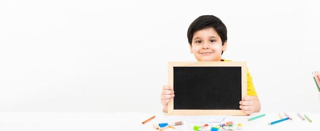 Cute smiling asian boy holding empty blackboard