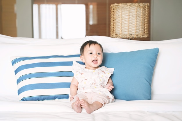 Cute smiling baby girl sitting on the bed.