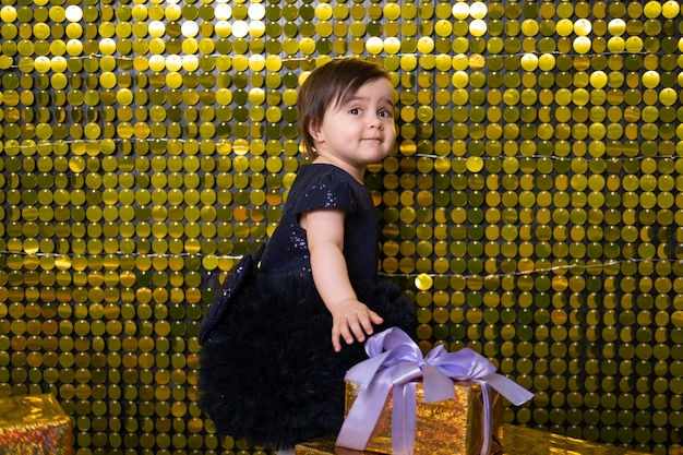 Cute smiling baby girl with gift boxes on background with gold shiny sequins, paillettes.