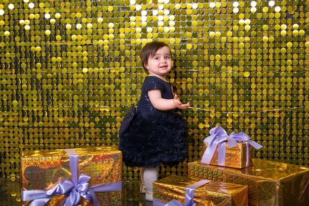 ゴールドの光沢のあるスパンコール、パイレットと背景にギフトボックスとかわいい笑顔の女の赤ちゃん。