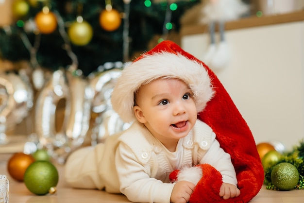 Симпатичный улыбающийся малыш лежит под праздничной елкой и играет с подарками