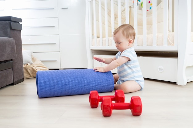 Cute smiling baby playing on floor with fitness mat and dumbbells. concept of child sports
