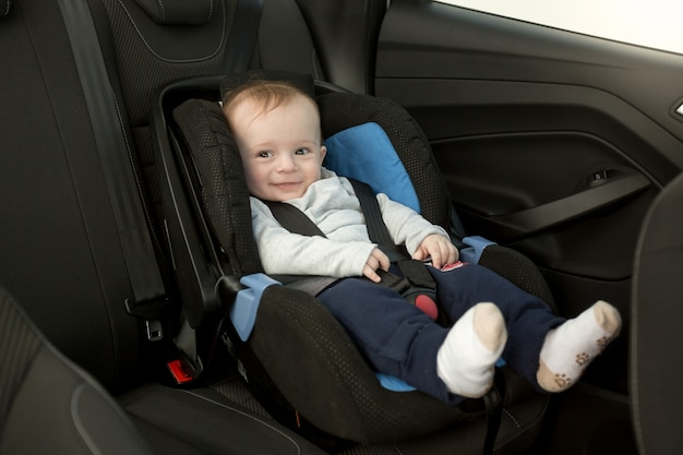 Cute smiling baby sitting in car seat