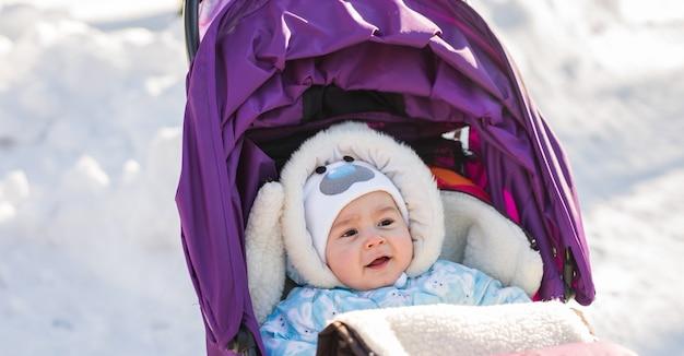 Милый улыбающийся ребенок сидит в коляске в холодный зимний день.