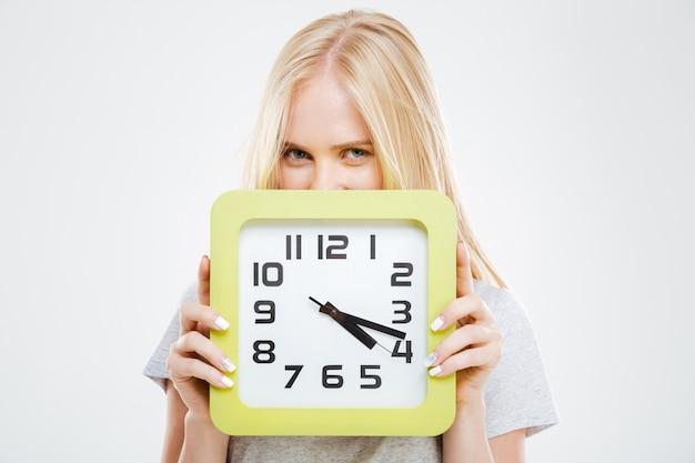 白い壁に隔離の壁時計から覗くかわいい笑顔のブロンドの女性