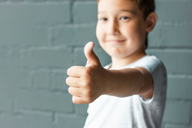 Cute smiling boy 8 years old showing thumbs up on background of grey brick wall