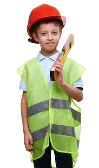 白い孤立した背景に水準器を測定する保護ヘルメットと建設ベストのかわいい笑顔の少年。将来の建設エンジニア。