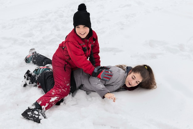Cute smiling boy playing with her sister on snowy land at winter day