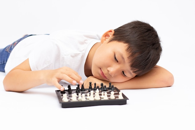귀여운 웃는 소년 흰색 절연 표면에 체스 판에 체스 조각을 보여줍니다