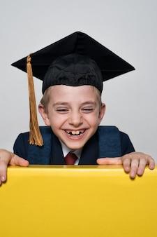 학생 모자를 입고 귀여운 웃는 소년. 쾌활한 남학생. 어린이 교육.