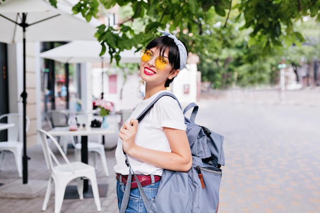 Cute smiling brunette girl with yellow sunglasses and leather belt carrying backpack while exploring city