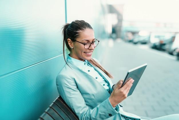 Мило улыбаясь брюнетка с очки, одетые в формальных износа, сидя на скамейке и с помощью планшета.