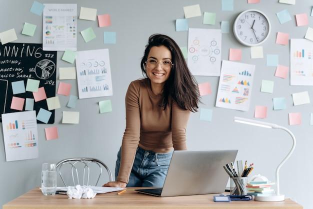 Симпатичная улыбающаяся деловая девушка в очках в офисе, опираясь на стол