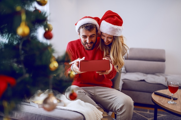 Cute smiling caucasian blonde woman giving christmas gift to her loving boyfriend. both having santa hats on heads. in foreground is fir tree. living room interior.