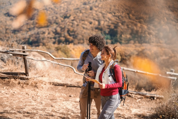 Cute smiling caucasian couple hiking. woman holding map, on backs backpacks.