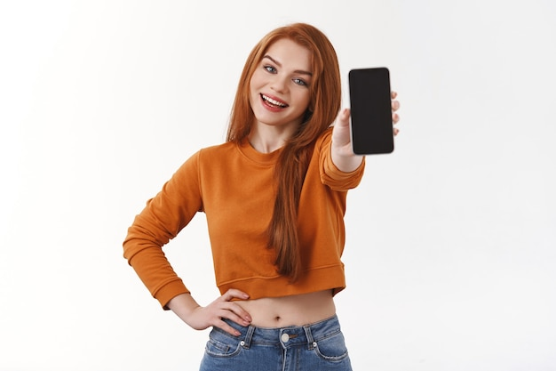 Cute smiling caucasian redhead female student in orange sweater, tracking her order online, showing cool photo she want post social media, holding smartphone, white wall