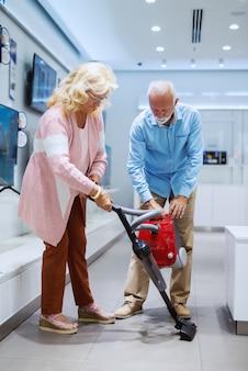 自宅に新しい掃除機を試すかわいい笑顔の白人の年配のカップル。テックストアのインテリア。