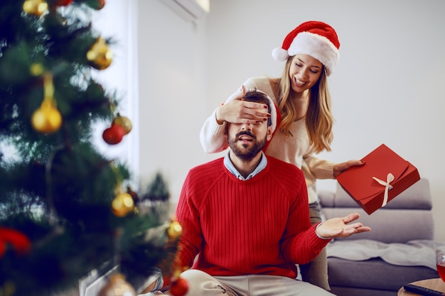 Cute smiling caucasian woman holding gift and covering her boyfriend's eyes