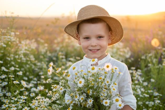 麦わら帽子のかわいい笑顔の子供の男の子は、日没時にフィールドカモミールの花束を保持しています。