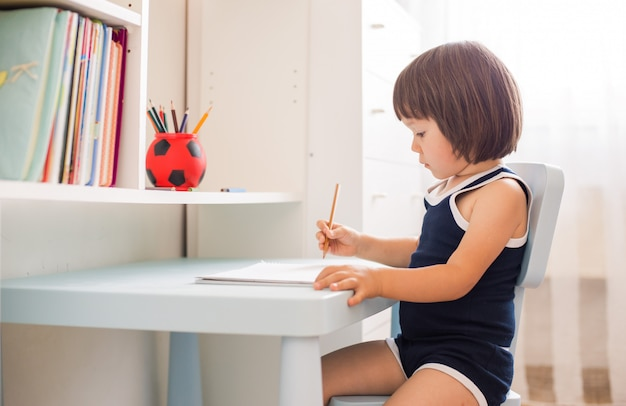 Cute smiling child doing homework, coloring pages, writing and painting