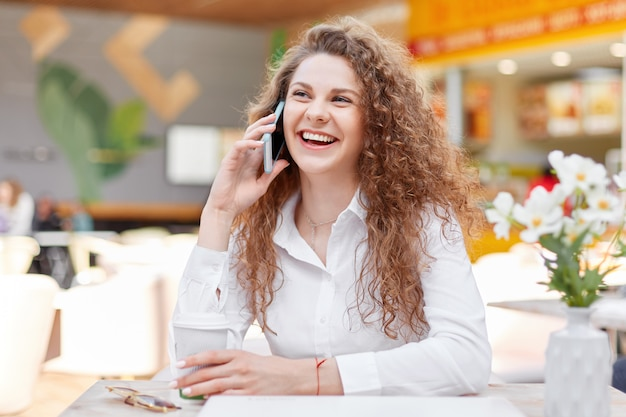 Cute smiling curly woman enjoys phone conversation with best friend