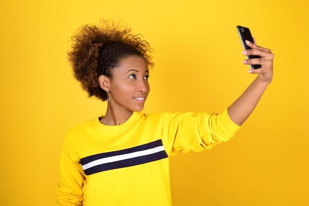 Симпатичная улыбающаяся темнокожая девушка в желтой толстовке с капюшоном делает селфи на своем смартфоне