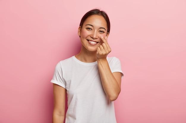 Симпатичная улыбчивая самочка трогает пальцем румяную кожу на щеках, демонстрирует ее мягкость, заботится о своей красоте, наклоняет голову, нежно улыбается, одетая в повседневную белую футболку, модели в помещении