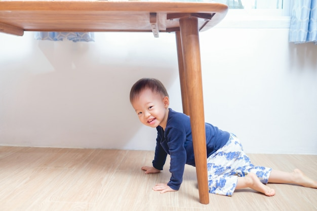 Cute smiling funny little asian 18 months / 1 year old toddler boy child playing under table at home looking at camera, kid has playful expression on his face, happy childhood concept