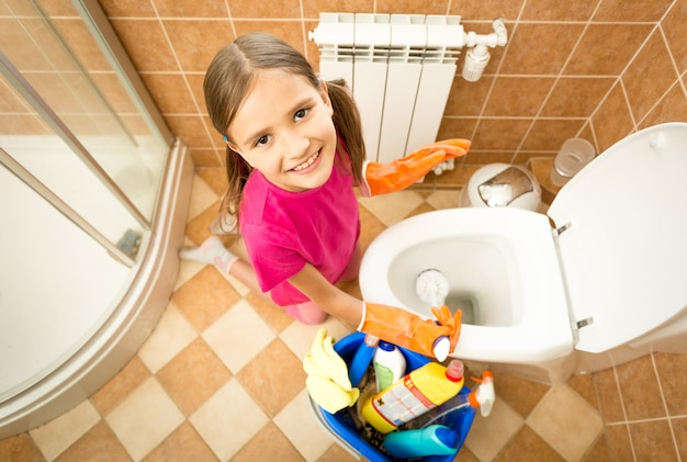 Cute smiling girl cleaning toilet with brush and looking at camera