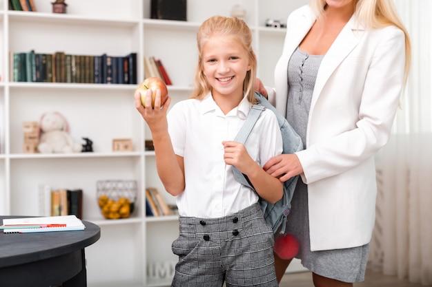 Милая, улыбающаяся девушка с яблоком в руке и рюкзаком на плечах хорошо позирует в комнате дома перед походом в школу